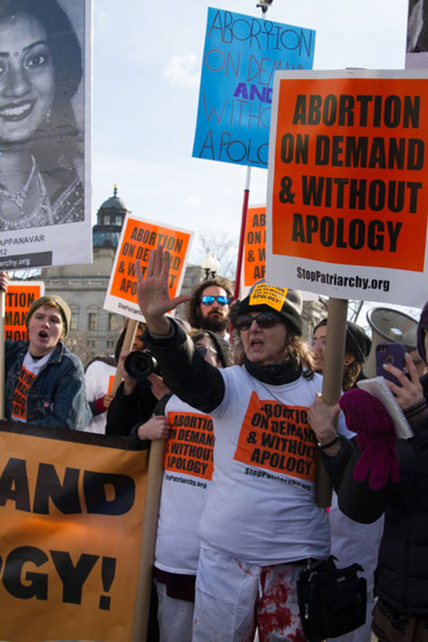 Women protestors hold up signs 'Abortion on demand and without apology.'