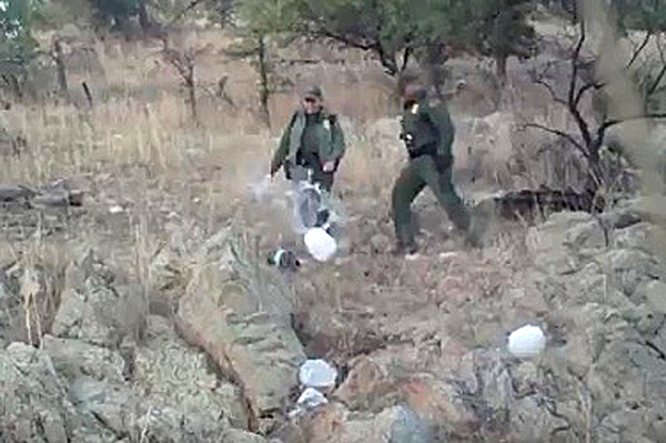 Border Patrol Agents kick over plastic jugs of water.