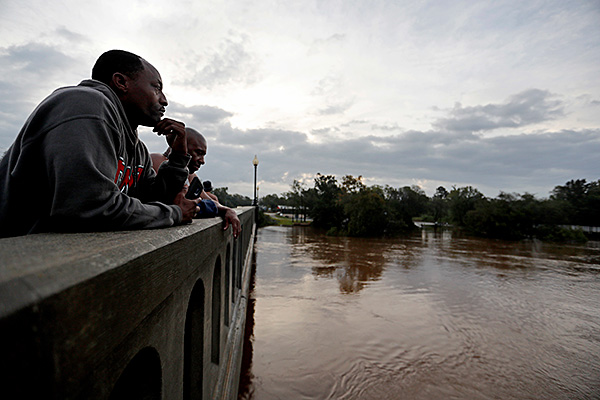 Floodwaters and storms, and their aftermath wreak their greatest havoc on poor, Black and oppressed peoples, and immigrants. Overlooking Cape Fear River, North Carolina, flooded by hurricane Florence, September 2018. (Photo: AP)