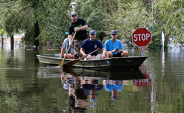 Residents of Lumberton navigate flooded streets in search of people who need help.
